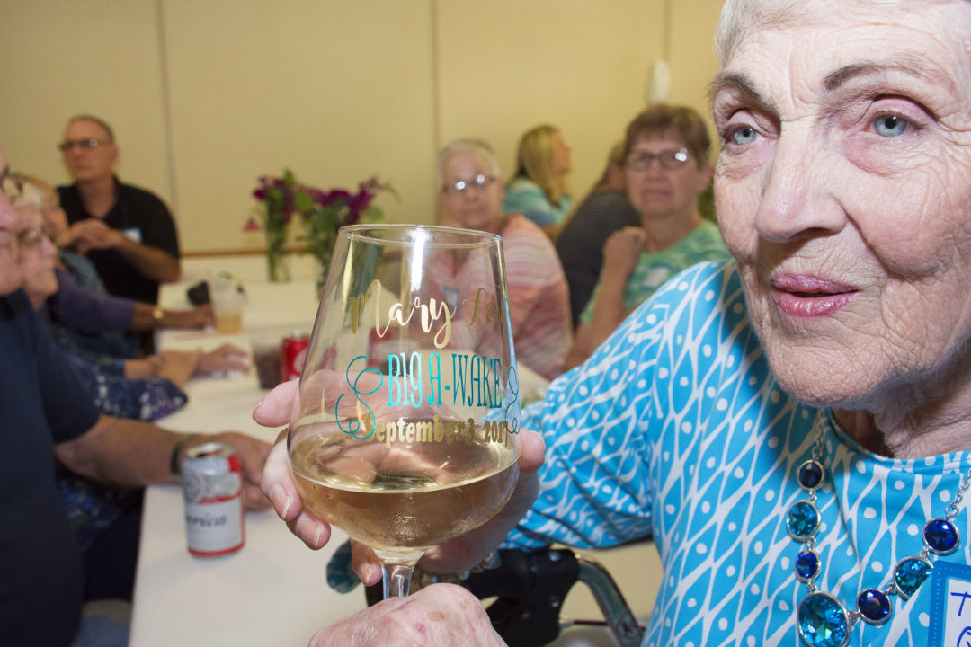 Mary shows off her customized wine glass for her special day, Big A-Wake